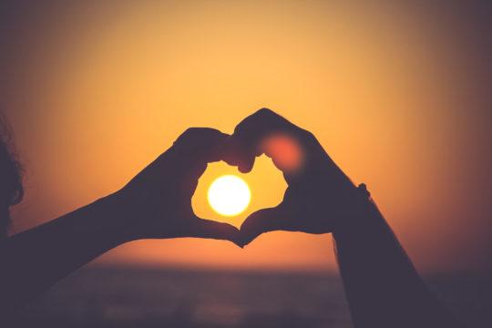 Photo de 2 mains formant un coeur  avec le soleil couchant à l'intérieur