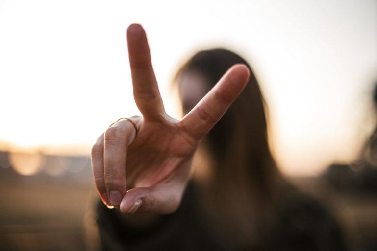 Photo de face d'une jeune fille faisant un V, le signe de la victoire avec ses doigts