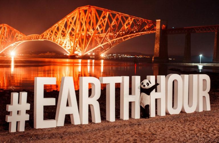 Photo du logo en 3D de Earth Hour avec une personnage portant un costume de panda devant un pont allumé de nuit