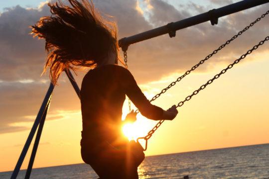 Photo de dos d'une jeune fille au bord de la mer faisant de la balançoire les cheveux au vent, devant un soleil couchant