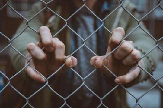 Photo d'une personne derrière un grillage atrrapant ce denier avec ses 2 mains