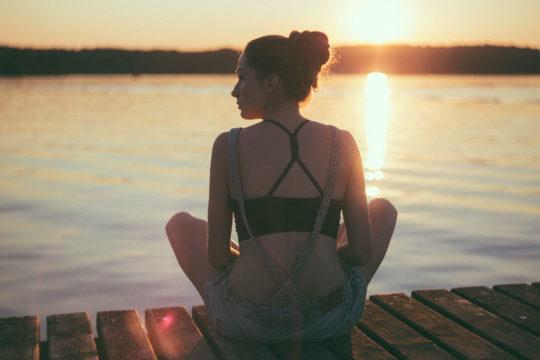 Photo d'une jeune fille de dos en assise au bord d'un ponton avec un soleil couchant à l'horizon