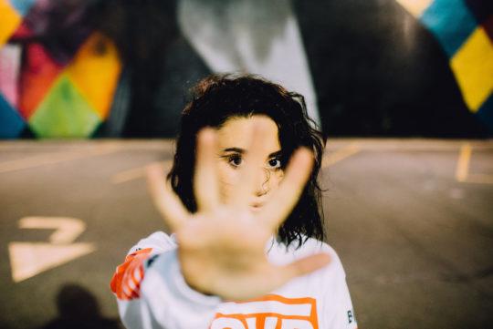 Photo de face d'une jeune fille faisant le signe stop avec sa main