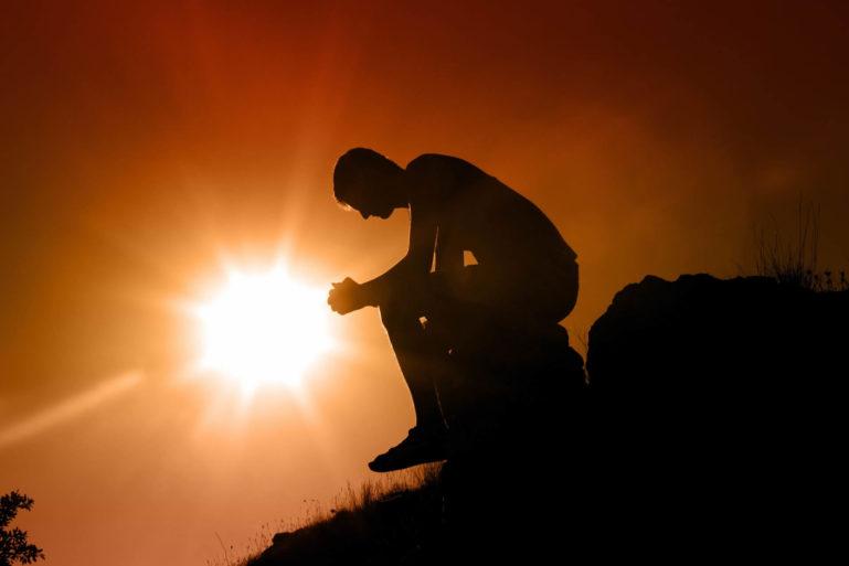 Photo d'une homme assis sur un rocher en mode penseur avec un soleil couchant derrière lui